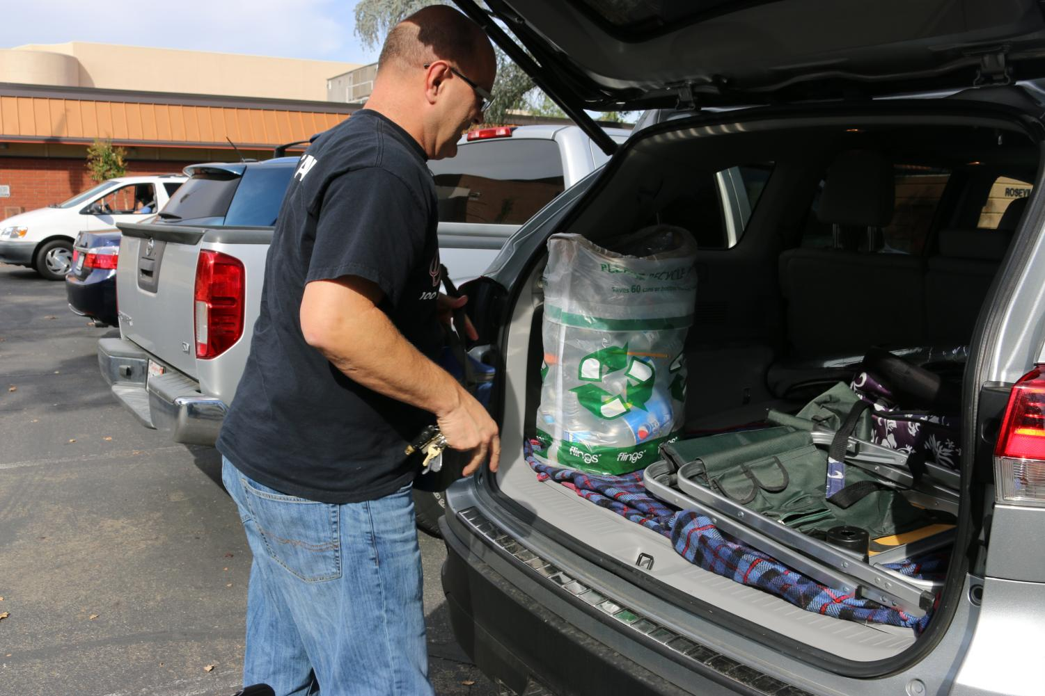 Math teacher David Ray takes out the recycling he's collected over the week and prepares to drive it out to a recycling center. He decision to begin recycling resides in a desire to get a head start on his son's college funds.
