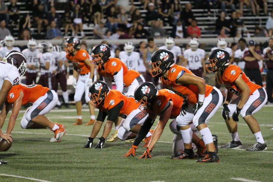 Roseville's defensive line prepares for Woodcreek's offense.