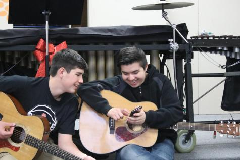 Students in the guitar class practicing in the band room. Guitar has relocated from their portable to the band room and cafeteria.