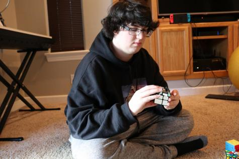 Senior Trey Driggs is in the midst of solving a Rubix Cube. Instead of speed, he aims to solve his puzzle cubes in as few moves as possible.