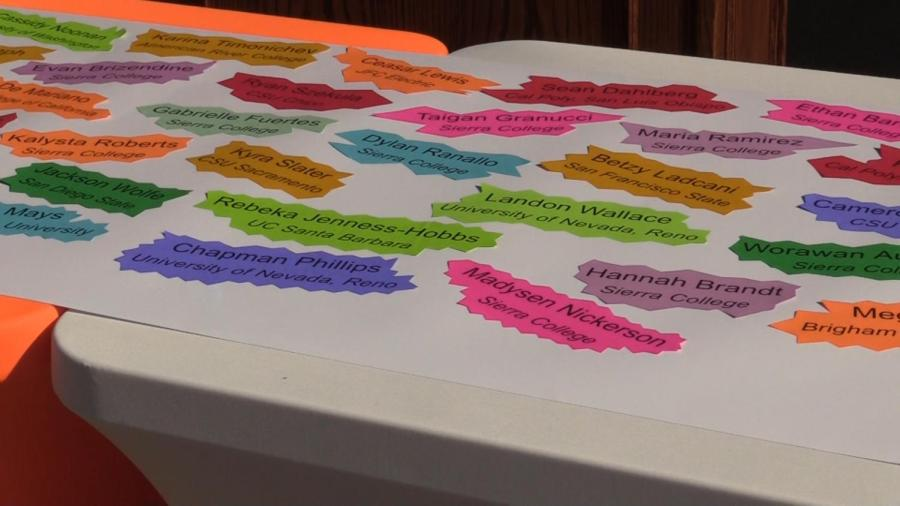 Senior's names and colleges laid out on a table. Due to school closures, college signing day is being held digitally.