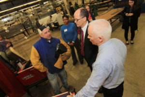 Third-year sheet metal apprentice Gregory Leonard, left, speaks with Thomas Perez, U.S. Secretary of Labor, center, and John Healy, training coordinator for Sheet Metal Workers Local No. 17, during a tour of the facility and round-table discussion on Nov. 17, 2014.