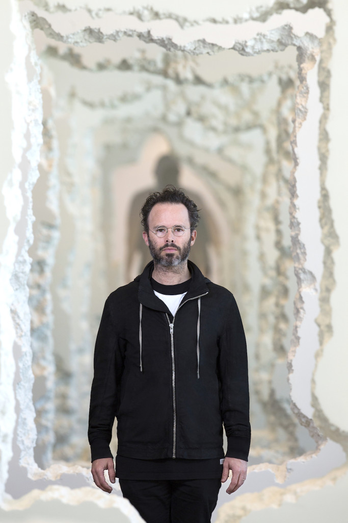 """Daniel Arsham in front of his work """"Wall Excavation"""" 2016, Styrofoam joint compound, Dimensions-variable. Commissioned by the SCAD-Museum-of-Art-Savannah. Photo courtesy of-SCAD Photography by John McKinnon"""