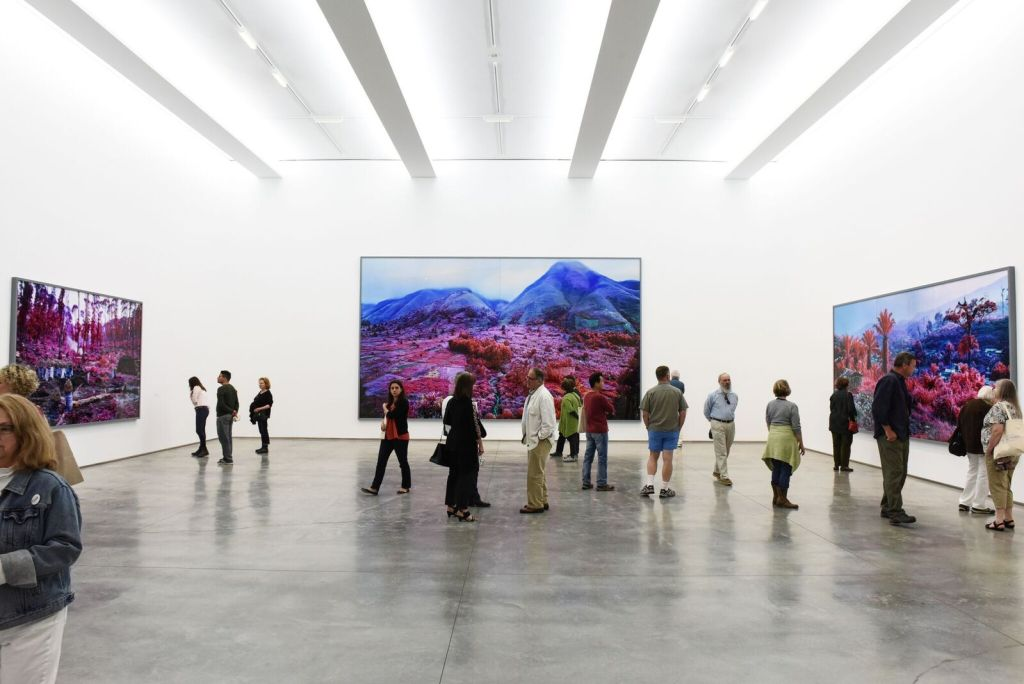 "Richard Mosse, Installation view, left to right: ""Hunches in Bunches,"" (2011) ""Everything Merges with the Night,"" (2015) and ""Hombo, Walikale,"" (2012). Image courtesy of Jack Shainman Gallery, photographed by Zach Hilty"