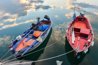 Two small wooden fishing boats in the port of Corigliano Calabro, Calabria, Southern Italy, under the sky at sunset reflected in the calm waters of the sea.