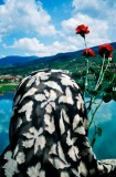 """SARA TERRY - A Muslim widow gets ready to throw red carnations in to the Drina River, marking the spot where some 2,000 Muslim men and boys were executed during the """"ethnic cleansing"""" campaign waged by Serbs against their neighbors in the early months of the 1992-95 war. The bridge, built during the Ottoman Empire, was made famous by the Nobel Prize-winning author Ivo Andric in his book, """"Bridge on the River Drina."""""""