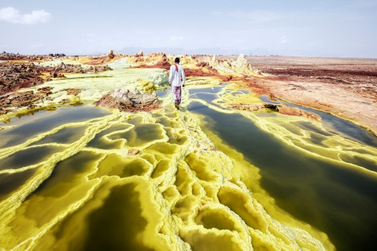 """Dallol, means the """"Hill of the Spirits"""" for the Afar people. Is the land of geysers, crystal formations and sulphurous springs. In this picture my guide in Dallol, Alì, walking through the landscape. Alì Arata (Afar ethnic group), 23 years old, lives in Hamed Ela, and for 10 years he has been working as a guide accompanying travelers to Dallol and to the volcano Erta Ela. Dallol is a volcanic explosion crater in the Danakil Depression, Ethiopia. These craters are the lowest known sub-aerial volcanic vents in the world, at over 45 m (150 ft) below sea level. Dallol is also known to be the hottest place on earth. The average daily-maximum_temperatures here could be of 110 °F. Acidic water, salt, sun, wind, impossible and violent rains have found a fertile desert for their art. Numerous hot springs are discharging brine and acidic liquid here. Widespread are small, temporary geysers, which are forming cones of salt. The term Dallol was coined by the Afar people and means dissolution or disintegration, describing a landscape made up of green acid ponds. © Andrea Frazzetta"""