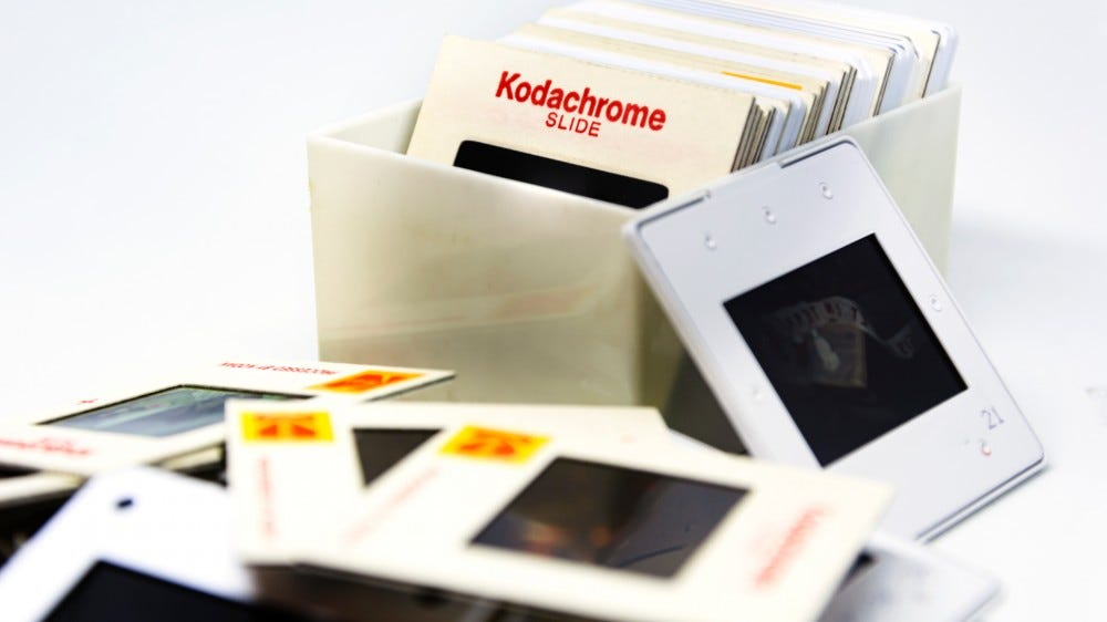 Group of Kodachrome brand slides from the 70s inside a plastic box and scattered on a table