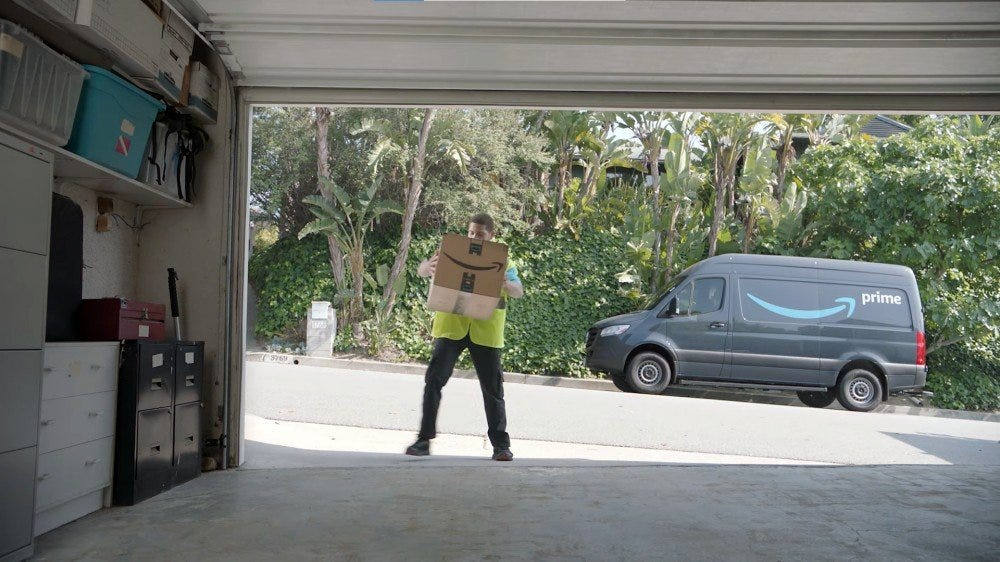 Amazon delivery person dropping of a box in a garage, with delivery truck parked behind them