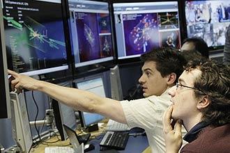 Cientistas observam gráficos sobre as primeiras colisões bem  sucedidas de energia total no Grande Colisor de Hádrons(LHC)