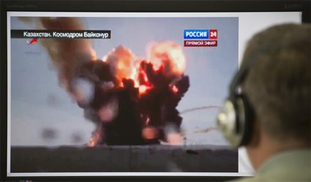 Homem observa em computador em Moscou a explosão do foguete russo Protón, que colocaria três satélites em órbita