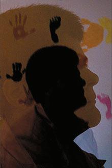 A enfermeira Gisele em frente a uma parede com marcas das mãos e pés do bebê gestado pela ex, com seus óvulos