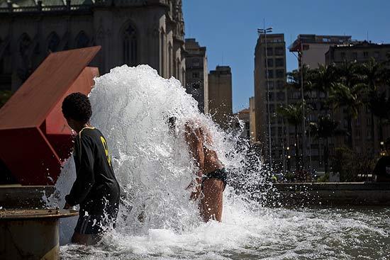 Crianças se refrescam em chafariz na praça da Sé (centro de São Paulo), onde não chove há cerca de 35 dias