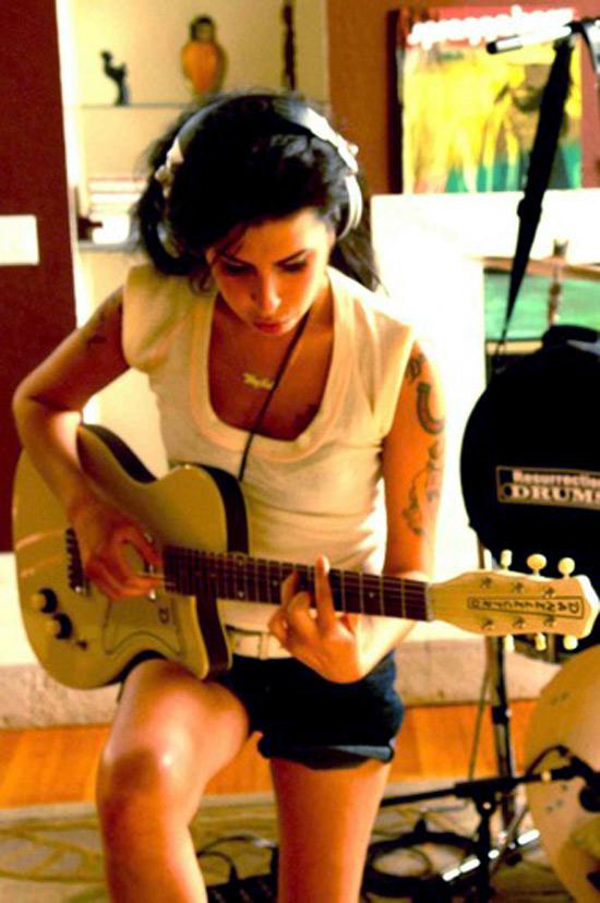A cantora Amy Winehouse toca guitarra em foto publicada pelo produtor Salaam Remi no Twitter