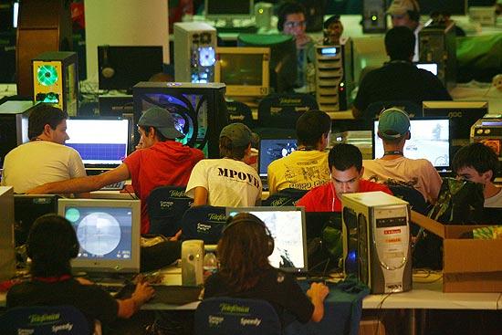 Jovens usam computador em evento de tecnologia; para analistas, máquinas para uso pessoal, incluindo profissionais liberais, seguram alta do mercado