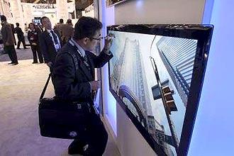 Homem examina tela LED em feira de Las Vegas; tecnologia toma o rumo das telas flexíveis e transparentes, afirma especialista