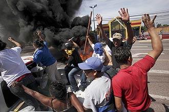 Apoiadores do presidente de Honduras, Manuel Zelaya, queimam pneus em protesto; militares aplicam golpe de Estado no país
