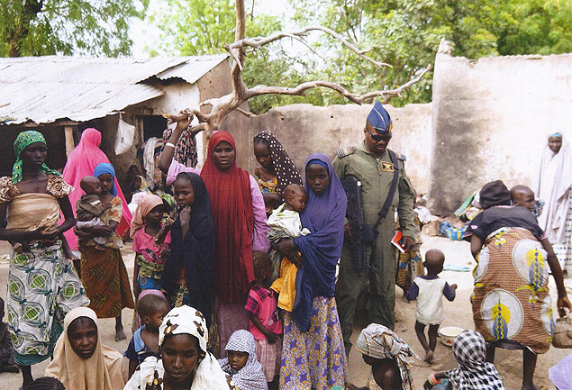 """BEST QUALITY AVAILABLE This handout picture released by the Nigerian army on April 30, 2015 and taken this week in an undisclosed location in the Sambisa Forest, Borno state, purportedly shows a member of the Nigerian Army standing next to a group of women and children rescued in an operation against the Islamist group Boko Haram. Boko Haram hostages were held in atrocious conditions in the group's Sambisa Forest stronghold, Nigeria's military said on April 30 after nearly 500 women and girls were released this week. AFP PHOTO / NIGERIAN ARMY -- RESTRICTED TO EDITORIAL USE - MANDATORY CREDIT """" AFP PHOTO / NIGERIAN ARMY """" - NO MARKETING NO ADVERTISING CAMPAIGNS - DISTRIBUTED AS A SERVICE TO CLIENTS -- ORG XMIT: NIGERIA04"""