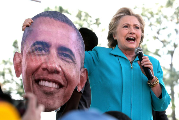 Democratic presidential candidate Hillary Clinton jokes with a giant image of President Barack Obama that was handed to her by a supporter while she delivered remarks to fans at the Bethune-Cookman University homecoming football game, in Daytona Beach, Fla., Saturday, Oct. 29, 2016. (Joe Burbank/Orlando Sentinel via AP) ORG XMIT: FLORL204