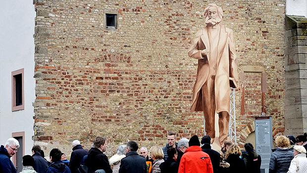 Moradores de Trier (Alemanha) observam representação em madeira de estátua chinesa de Karl Marx