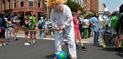 FILE PHOTO: A protester in a costume depicting Trump sets an Earth on a tee as he holds a golf club while joining demonstrators moving down Pennsylvania Avenue during a People's Climate March, to protest U.S. President Donald Trump's stance on the environment, in Washington, U.S., April 29, 2017. REUTERS/Mike Theiler/File Photo ORG XMIT: ROP330