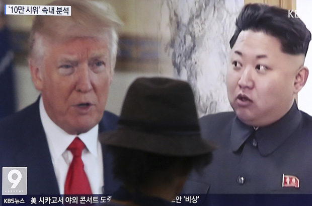 Homem vê um programa de TV em Seul que mostra Donald Trump e Kim Jong-un