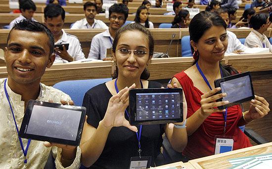 Estudantes exibem o Aakash, tablet mais barato do mundo, em evento em Nova Déli