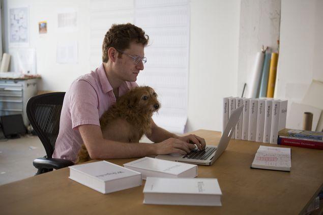 Michael Mandiberg com seu cachorro, Freddie Merckx, e volumes da Wikipédia em seu estúdio em Nova York