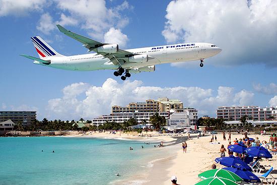 Avião sobrevoa a praia Maho Beach, na ilha de St. Marteen, no Caribe, em direção ao aeroporto Princess Juliana