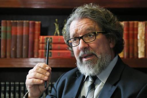 O advogado criminalista Antônio Carlos de Almeida Castro, conhecido como Kakay, ergue uma caneta em frente a uma estante de livros