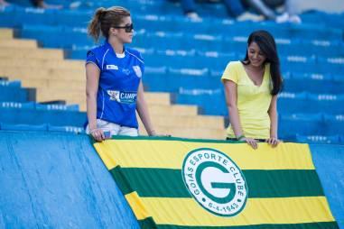 Torcedora ao lado de bandeira com o símbolo do Goiás no estádio Serra Dourada