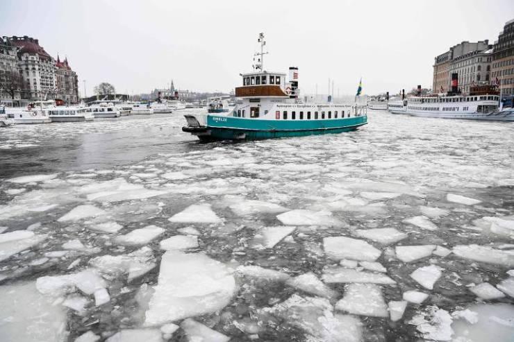 Barco navega na baía de Nybroviken, na capital sueca, Estocolmo, durante o inverno