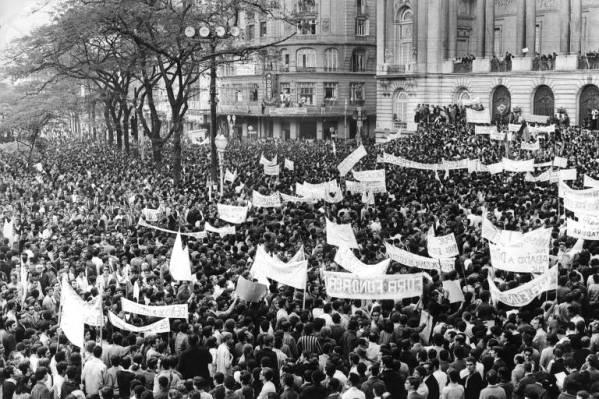 Multidão carregando faixas, em foto em preto e branco