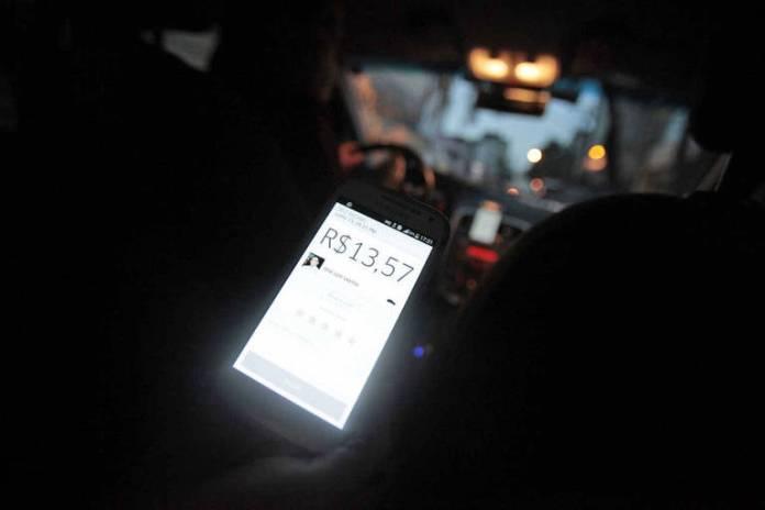 Passageiro mostra valor da corrida em carro da Uber