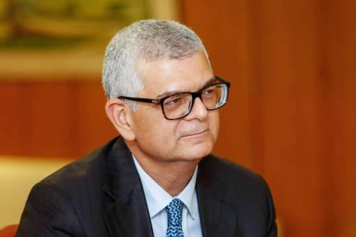 Ivan monteiro usa terno preto com gravata azul e camisa branca. Ele também está com óculos de grau quadrado, com armação preta