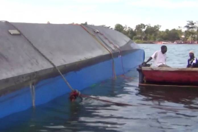 Equipe de resgate ao lado de balsa que virou no Lago Victoria, na Tanzânia