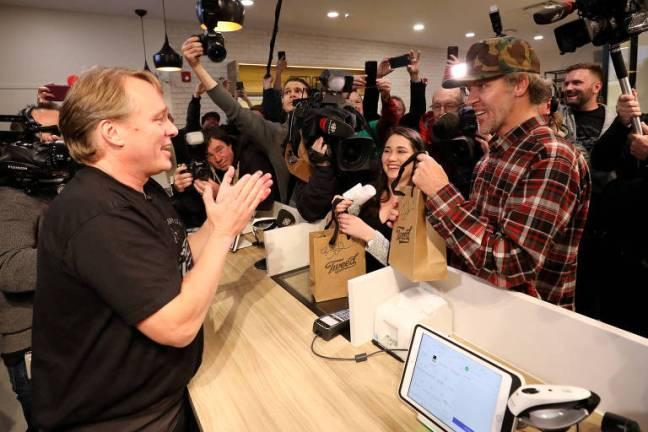 Logo após a meia-noite, Ian Power (dir.) recebe do executivo Bruce Linton seu pacote com maconha em St. John