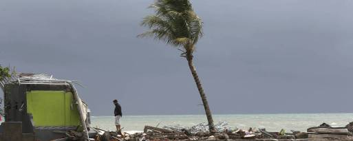 Homem observa rastro da destruição provocada pelo tsunami na praia de Carita, na Indonésia