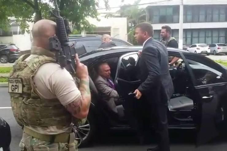 O ex-presidente Michel Temer é conduzido por policiais até o carro em frente a sua casa em São Paulo na manhã desta quinta-feira (21)