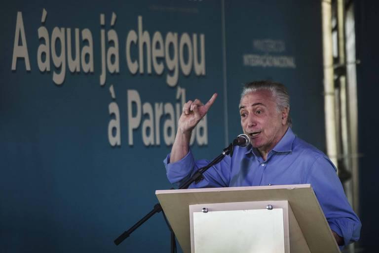 O então presidente Michel Temer inaugura o trecho lesre da transposição do São Francisco em Monteiro (PB); ele discursa na frente de uma placa, que diz: A água já chegou à Paraíba