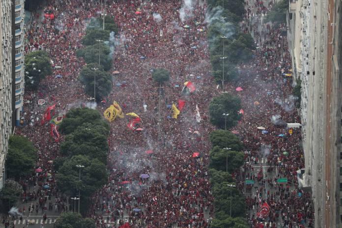 Torcedores lotam a avenida Presidente Vargas e soltam fogos para receber o time do Flamengo, que desfila em carro aberto durante comemoração do bicampeonato da Libertadores