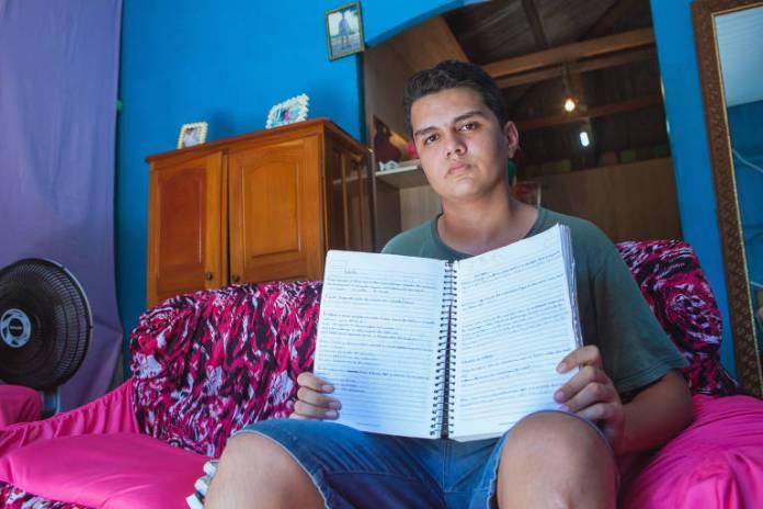 Um adolescente está sentado em uma cama e segura um caderno escolar