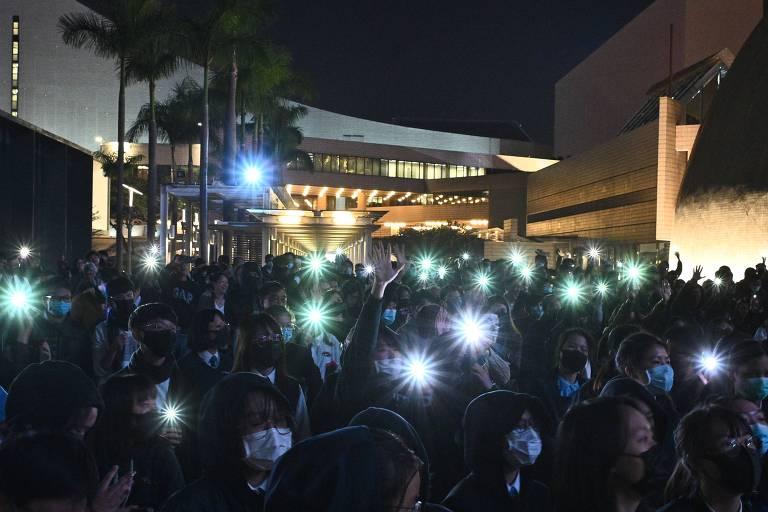 Estudante com luzes de telefones celulares durante protestos pró-democracia em Hong Kong