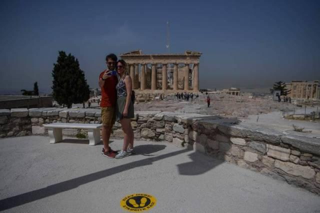 Casal posa para foto ao lado de adesivo que indica necessidade de distanciamento social em frente ao Partenon, na Acrópole, em Atenas (Grécia); sítios arqueológicos foram reabertos no país