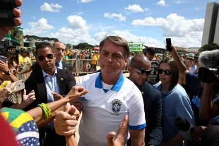 No dia 15 de março, o presidente Jair Bolsonaro cumprimenta apoiadores em manifestação que critica o Congresso e o Supremo Tribunal Federal, na frente do Palácio do Planalto