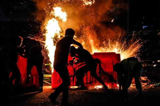 Manifestantes se protegem atrás de barricadas durante confrontos com a polícia em protesto na cidade de Cucuta, na Colômbia