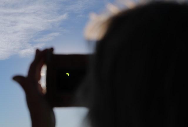 Una persona observa el Sol con un vidrio especial durante eleclipsesolar total, este martes en la ciudad de Merlo, San Luis (Argentina).