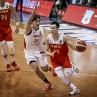 China guard Zhao Jiwei drives to the hoop while guarded by Japan's Daiki Tanaka during their FIBA Asia Cup qualifying contest on Saturday.  | COURTESY OF FIBA ASIA CUP