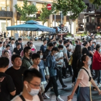 Shoppers and pedestrians walk along Nanjing Road in Shanghai on June 6. | BLOOMBERG