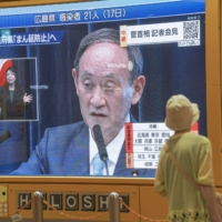 A large screen in Sapporo shows Prime Minister Yoshihide Suga speaking at a news conference in Tokyo on Thursday. | KYODO